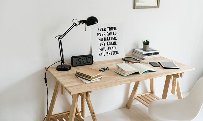 Student's wooden desk with assignment and paperwork on it. A motivational poster with black bold text over white background stands leaning against wall. I black lamp also stand on desk.