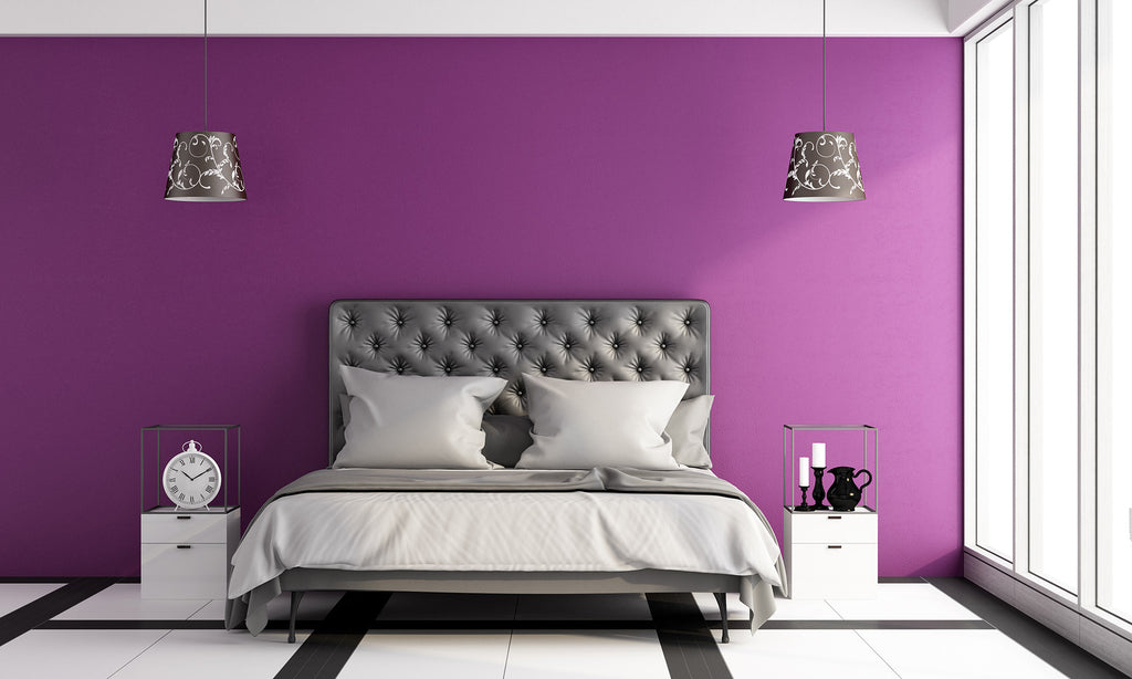 Bedroom with purple TemPaint wallpaper, two gray lamps above bed, and two short white nightstands beside bed. White tile floor and ceiling.