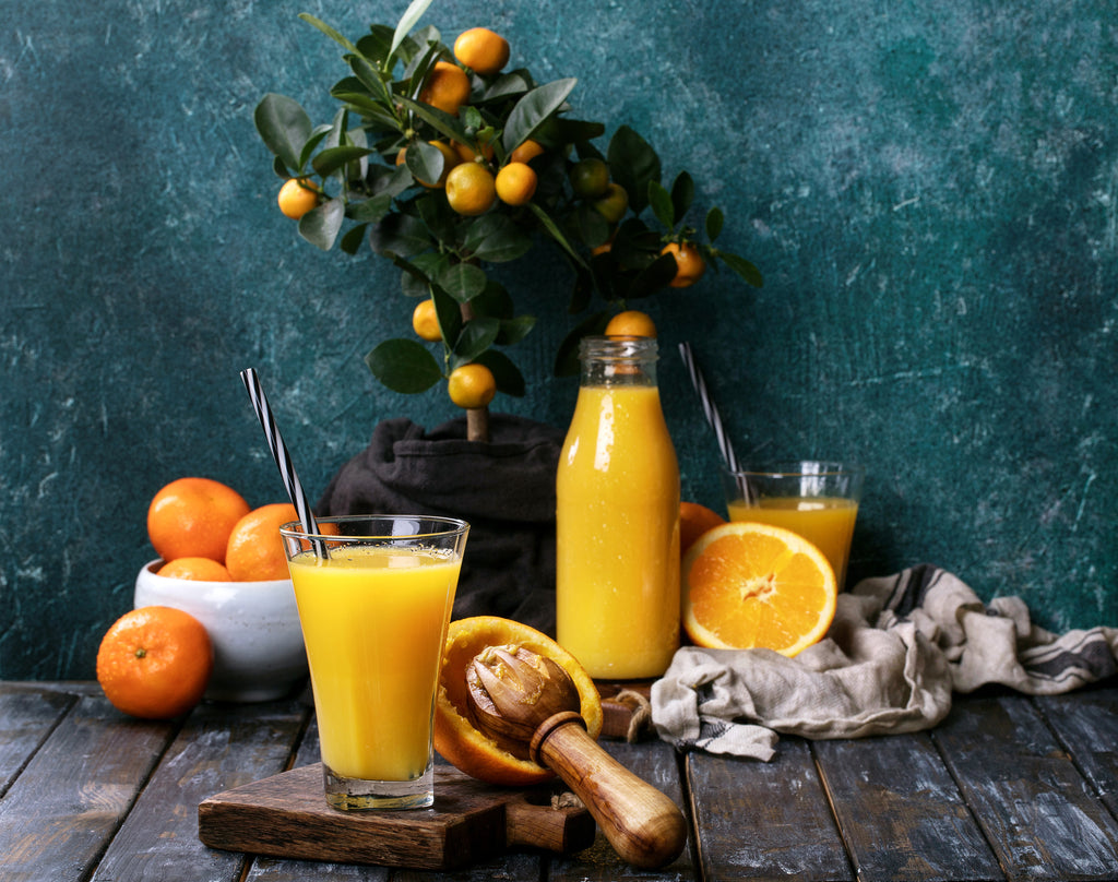 Orange juice and oranges on tree with elegant wallpaper.