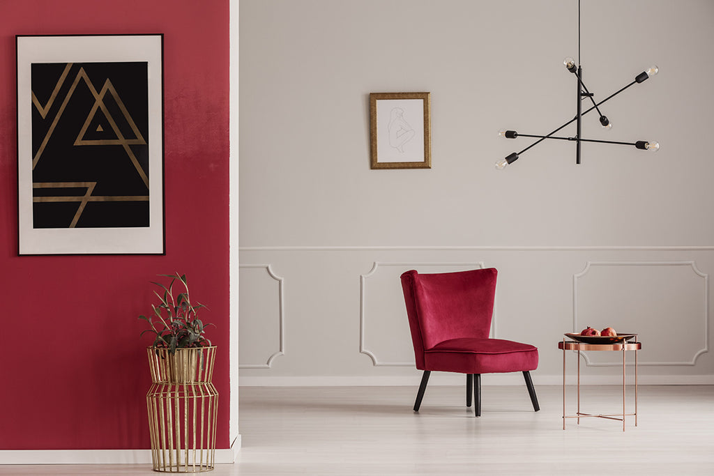 Partitian accent wall with one portion painted white, while another in Milano red. A red chair stands next to a small wooden coffee table. A tall vase with flowers stands in front of red wall with portrait painting hanging from wall.