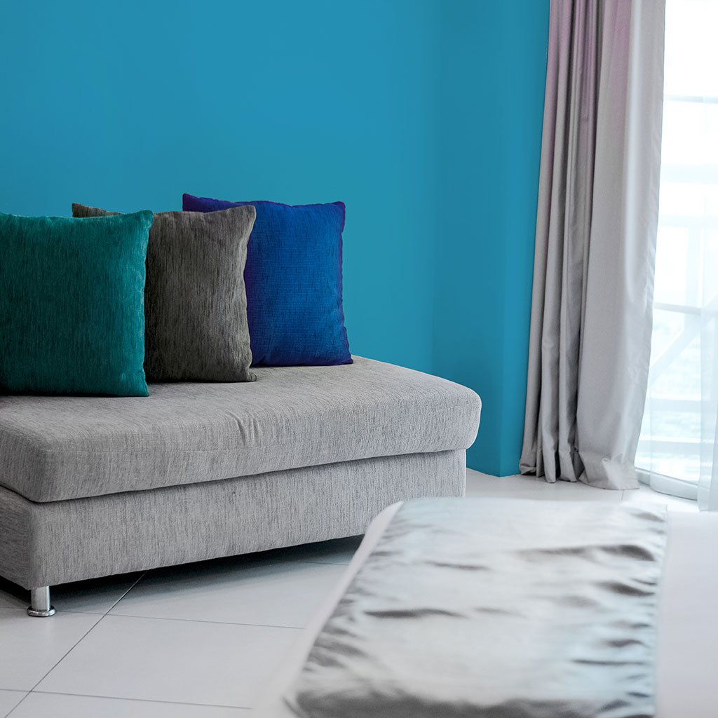 Bright blue peel and stick removable paint and bright blue solid color wall paper in apartment living room - Monterrey Blue TemPaint