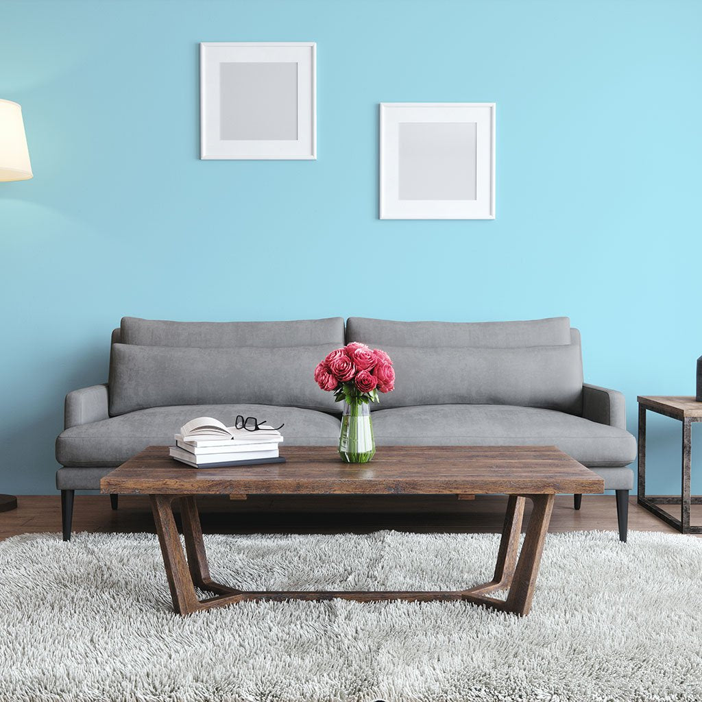 Light blue peel and stick removable paint and solid light blue wall paper in living room with gray couch - Savannah Blue TemPaint