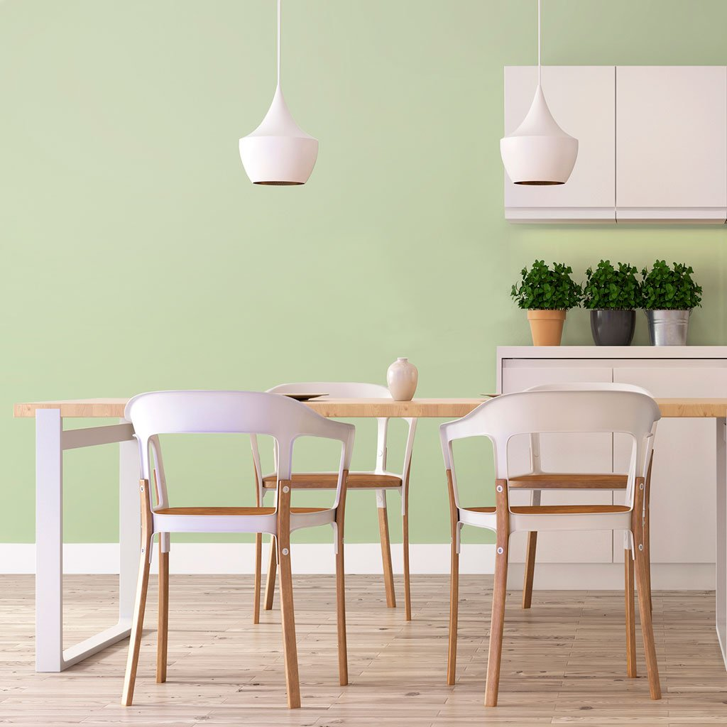 Light green peel and stick removable paint and solid light green wall paper in kitchen behind dinner table with white wood chairs  - Frosted Green TemPaint