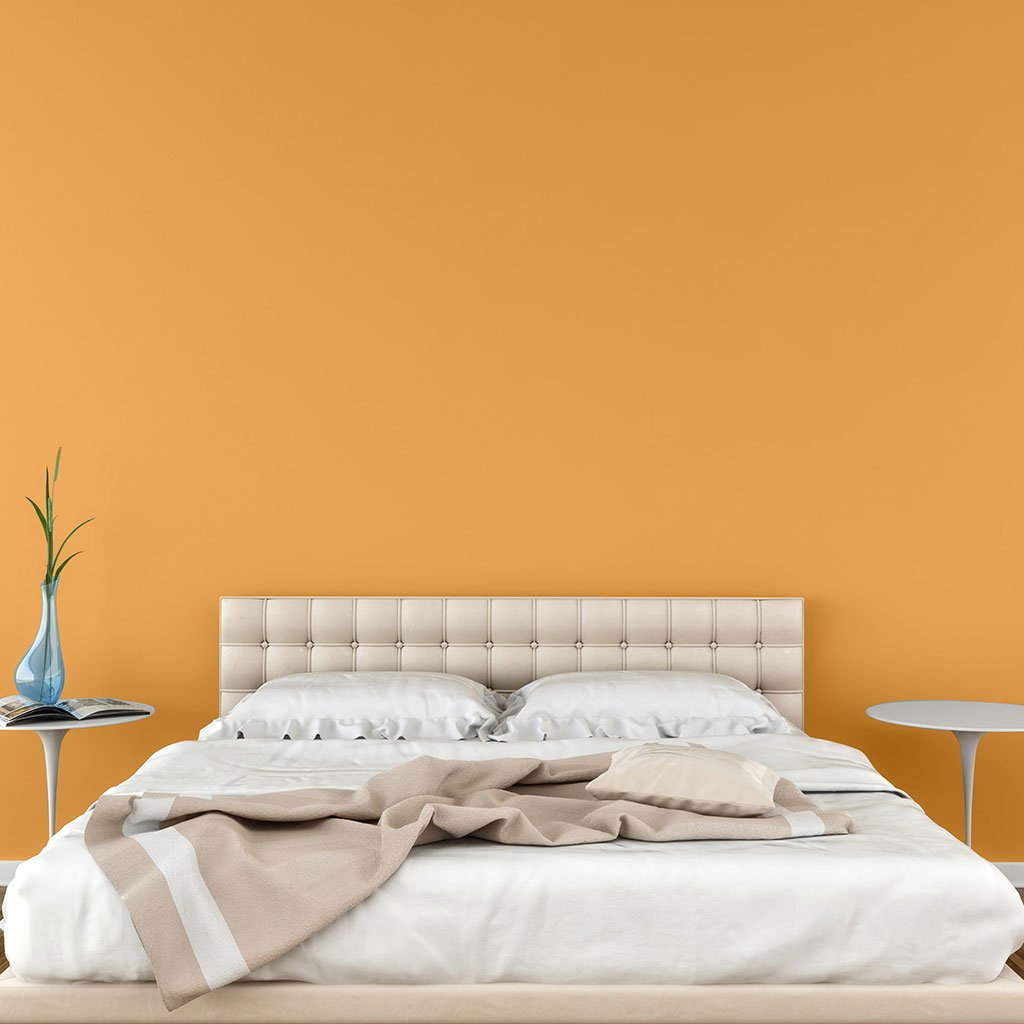 Orange peel and stick removable paint and solid orange wallpaper in bedroom behind white bed - Santa Fe Orange TemPaint