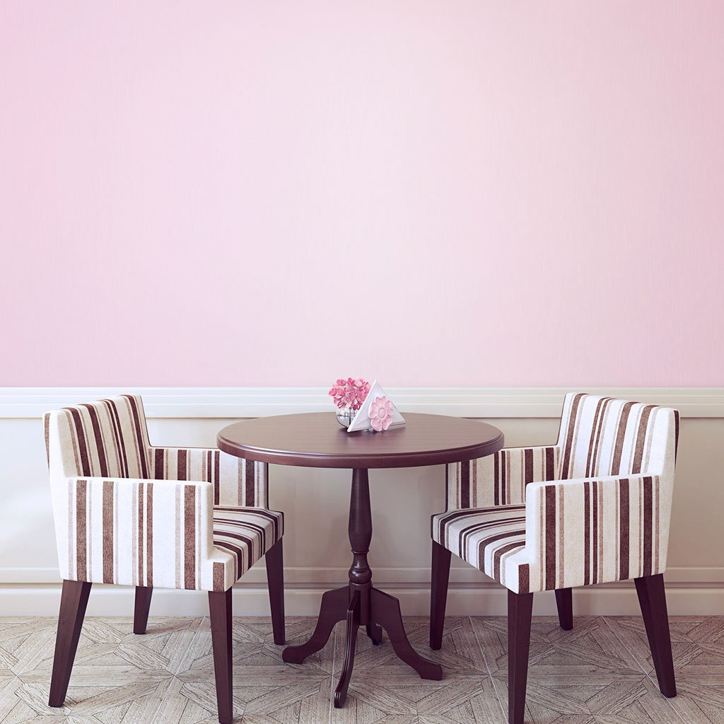 Pink peel and stick removable paint and solid pink wallpaper behind small table and two designer sitting room chairs - Pensacola Pink TemPaint