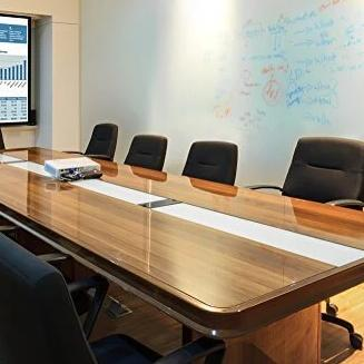 Large TemPaint dry erase board on wall of corporate office space with large wooden meeting table and chairs.