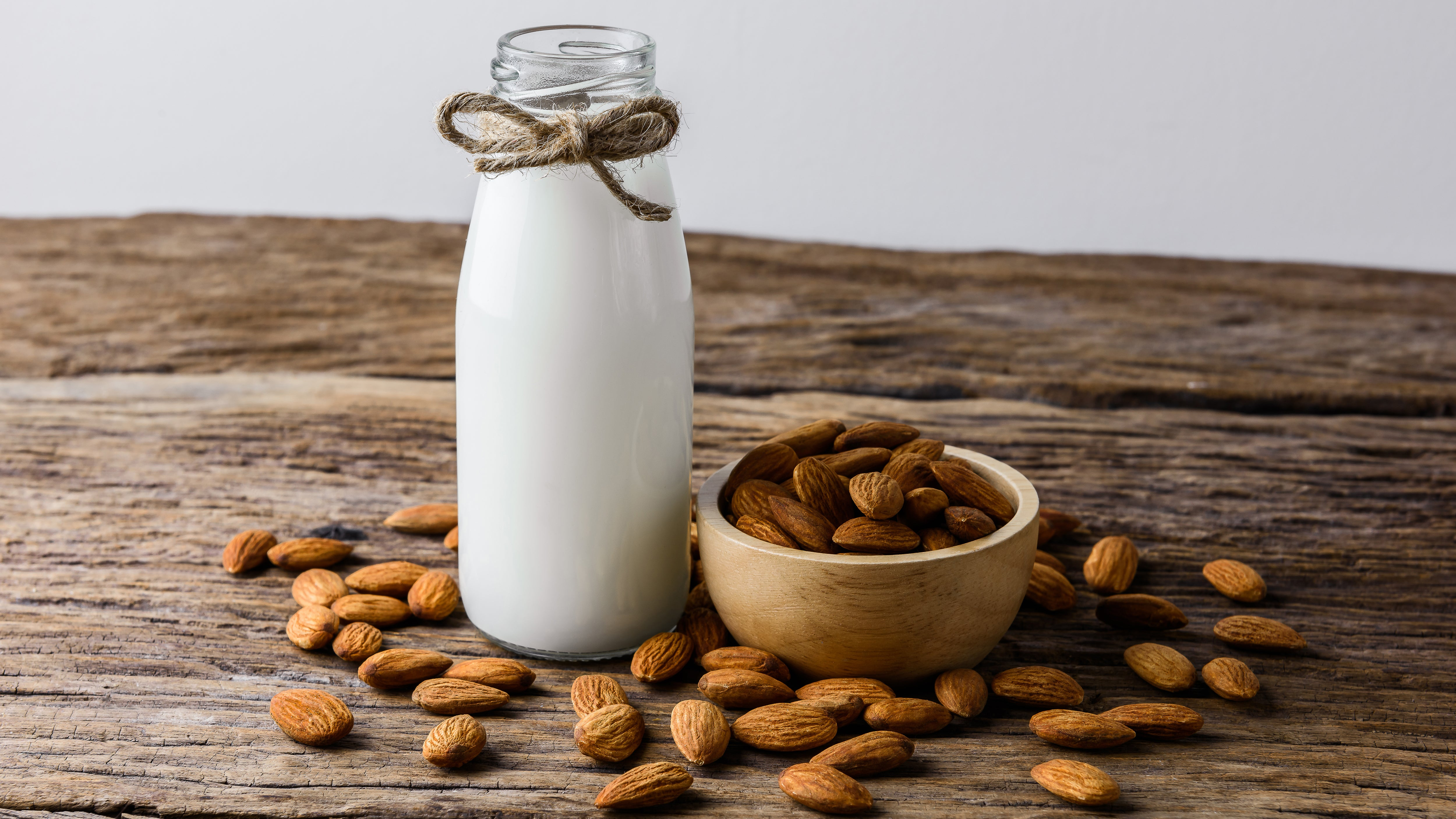 glass container filled with almond milk and a bowl of raw almonds