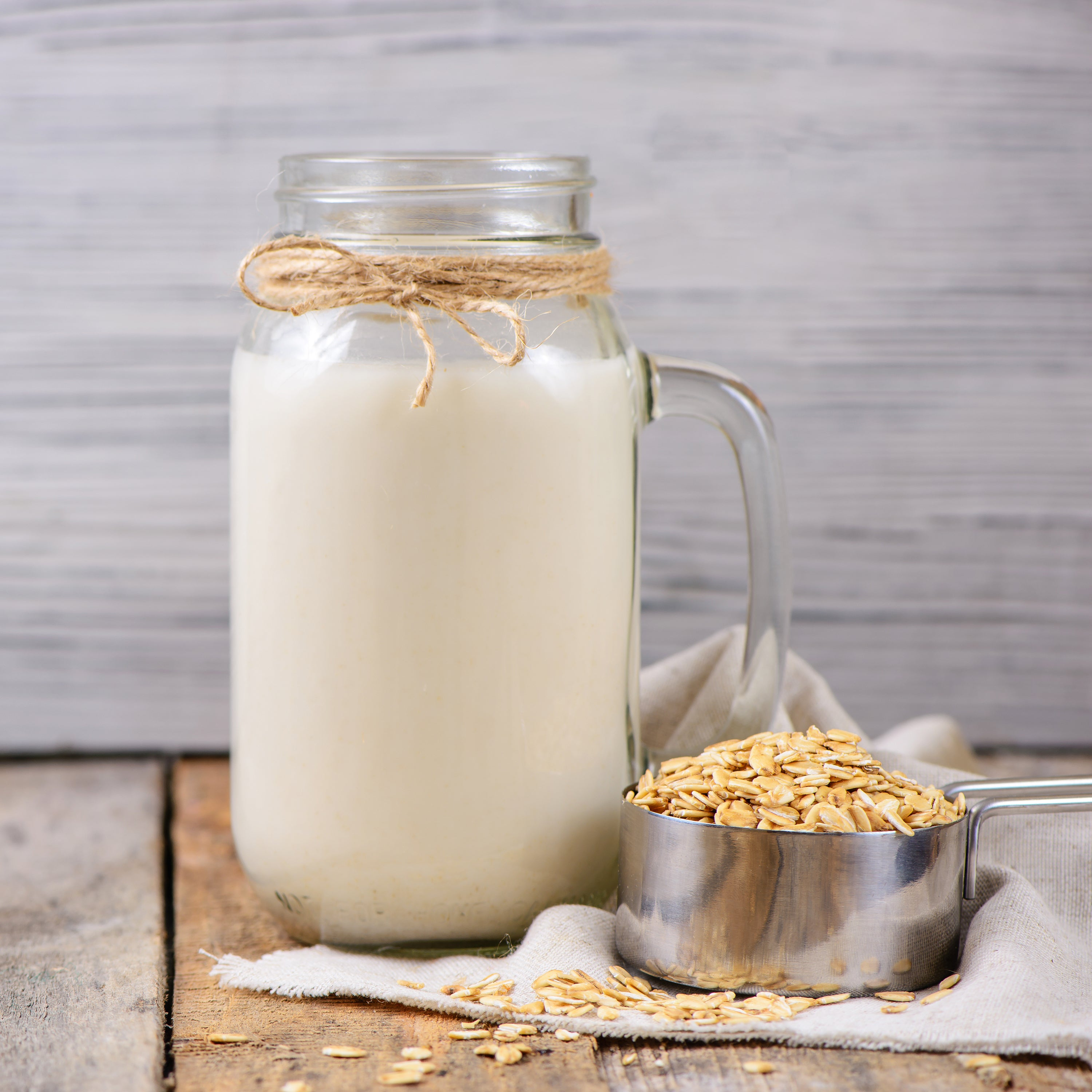 glass containers of oat milk and a measuring cup filled with oats