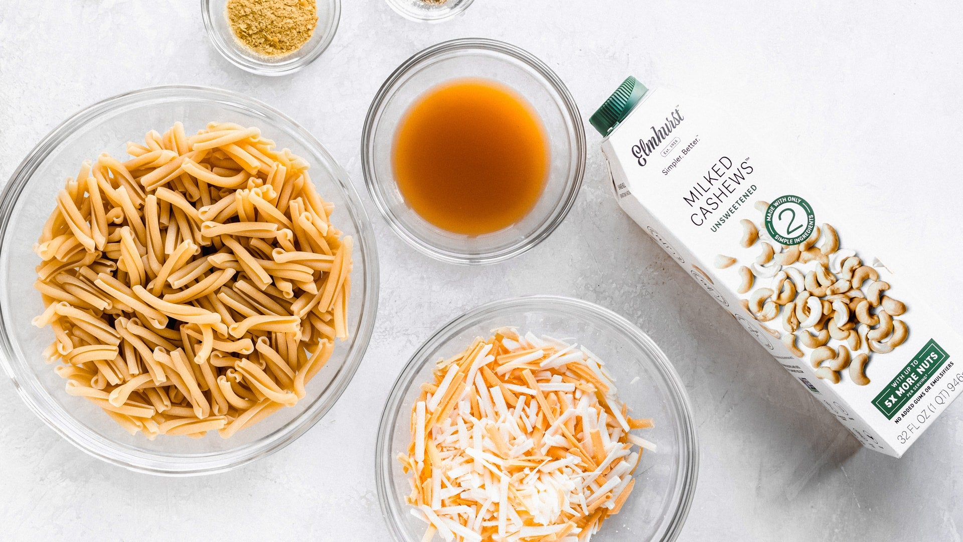 a bowl of dry pasta, mixed shredded cheese and a carton of cashew milk