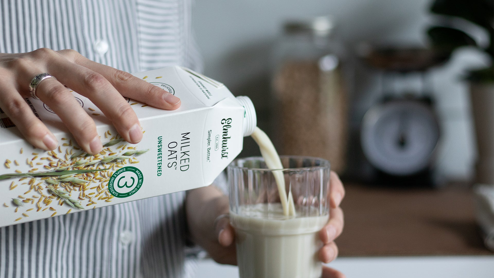 a man pouring a glass of unsweetened oat milk