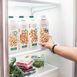 Unsweetened Cashew Milk, Unsweetened Almond Milk, Unsweetened Walnut Milk and Barista Approved Cashew Milk inside a fridge