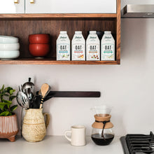 Load image into Gallery viewer, Elmhurst's varieties of shelf-stable oat milk coffee creamers sitting on a shelf