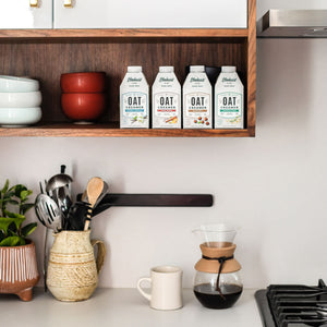 Elmhurst's varieties of shelf-stable oat milk coffee creamers sitting on a shelf