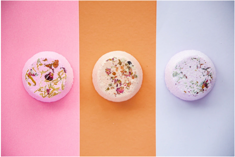 Colorful CBD bath bombs on pastel pink, orange, and blue backgrounds