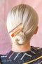1 lilac and burnt orange enamel hair clip set in blonde hair styled in a bun updo.