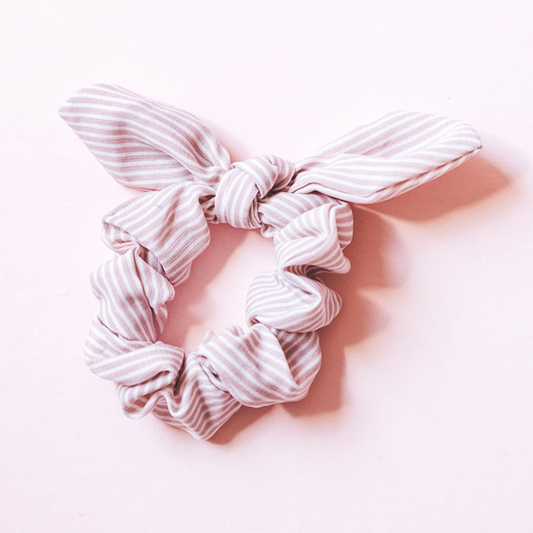 Light pink pinstripe patterned scrunchies with a bow. Made of polyester and is very stretchy. More classic pinstripe but in an unexpected color—pink! The most casual way to dress up an outfit ever! This bow scrunchie is a cute accessory to keep around your wrist when it's not in your hair.