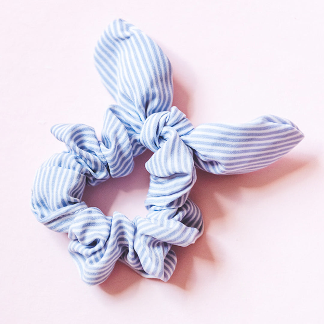 Light blue pinstripe patterned scrunchies with a bow. Made of polyester and is very stretchy. Want a pattern that is subtle enough to throw on with anything? This pinstripe in blue is as classic as it gets! Style it in your hair or put it around your wrist! A perfect accessory.