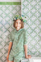 Paper shamrocks and paper flower templates to make a shamrock wreath crown. Green floral outfit with a geometric tile backdrop