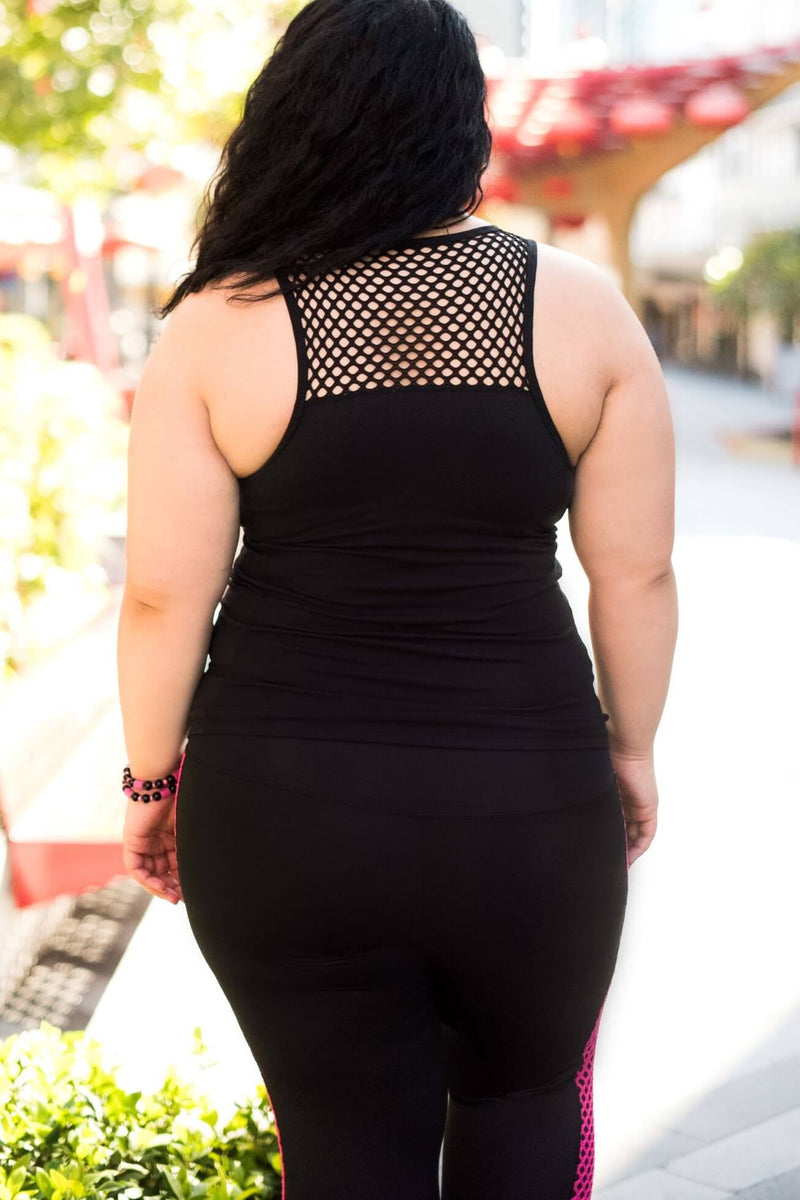 Model is shown from the back wearing black leggings which have a pink mesh pattern down the length of each side. The leggings are 7/8 in length, and she also wears a tight black tank top with a mesh trim on the chest.