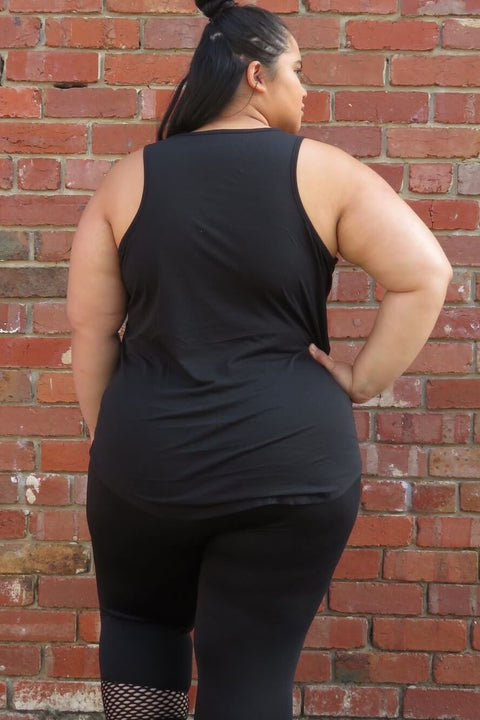 Girl wearing a black tank, down to the hips. The tank reads 'Bitch Please'. She is also wearing black leggings. In this picture she has her back turned, and the tank covers her back, and covers her bottom.