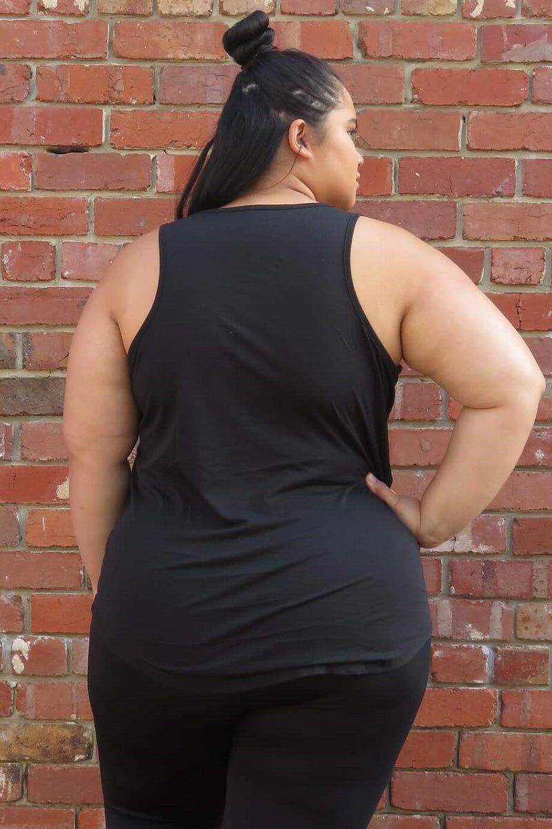 Girl wearing a black tank, down to the hips. The tank reads 'Badass Babe'. She is also wearing black leggings. In this picture she has her back turned, and the tank covers her back, and covers her bottom.