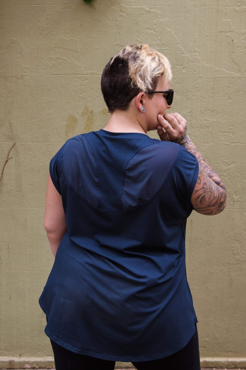 Female model is shown from the back and wears a charcoal top with longer length, extended sleeve and racer style back with mesh panels for coverage. She also wears black leggings.