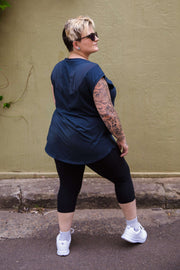 Female model is shown from the back wearing black capri length leggings, paired with a charcoal hip length top with mid-length sleeves.