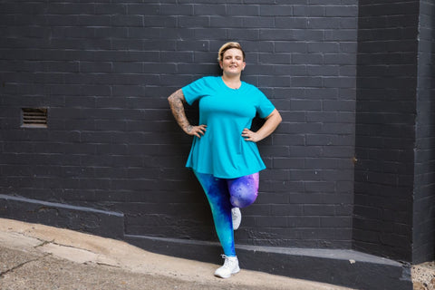 Model wears aqua swing style top with mid-length sleeves, loose fit. Worn with blush full length leggings.