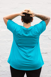 Model is shown from the back and wears aqua swing style top with mid-length sleeves, loose fit. Worn with black leggings.