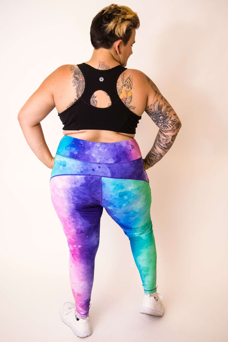 Model is shown with her back turned wearing full length leggings, which have a pattern of blues, greens, purples and pinks blurred together. She also wears a black crop top.