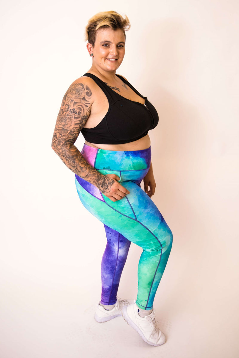 Model is wearing full length leggings, which have a pattern of blues, greens, purples and pinks blurred together. She also wears a black crop top.