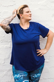 Female model wears a navy swing style top with mid-length sleeves, loose fit. Worn with blue sea-patterned leggings.