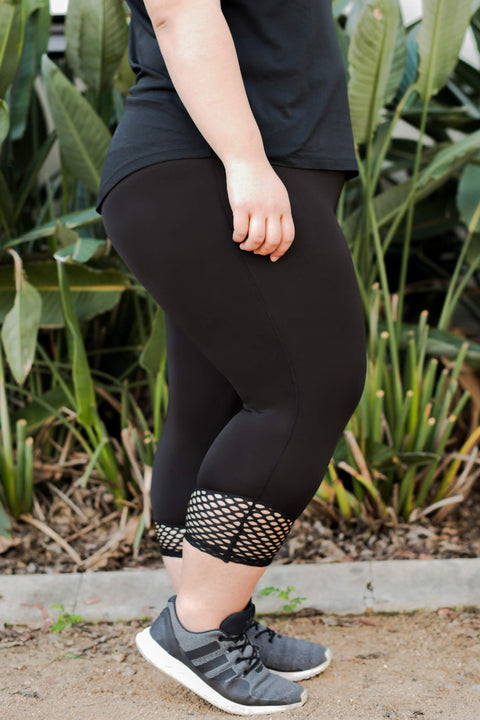 Model wears black leggings with a mesh cuff, that cuts off at approximately 7/8 length.