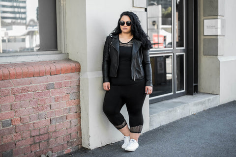 Female model wears black leggings with a mesh cuff, that cuts off at approximately 7/8 length. She is also wearing a let's get meshy top in black with a black leather jacket over the top.