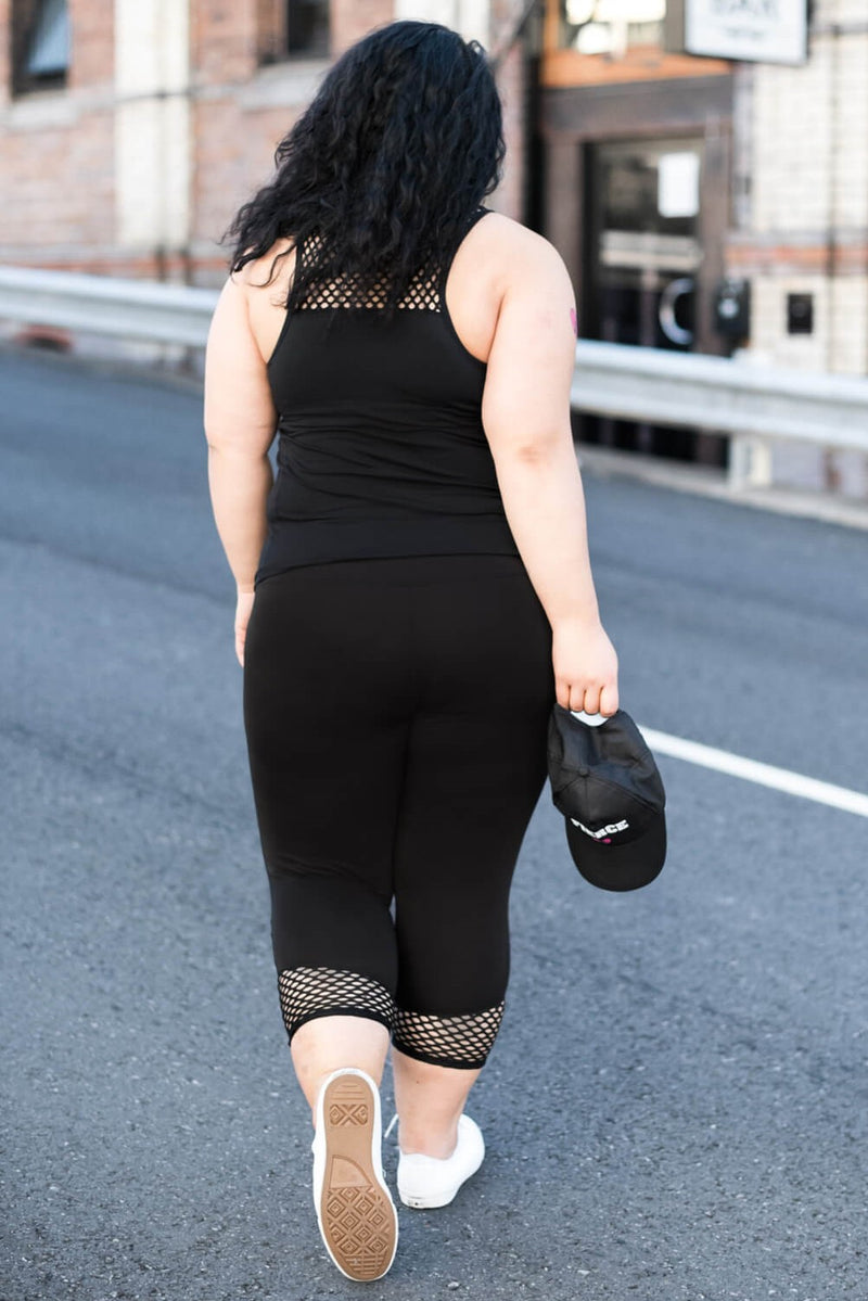 Model is shown from the back and wears black leggings with a mesh cuff, that cuts off at approximately 7/8 length. She is also wearing a let's get meshy top in black.