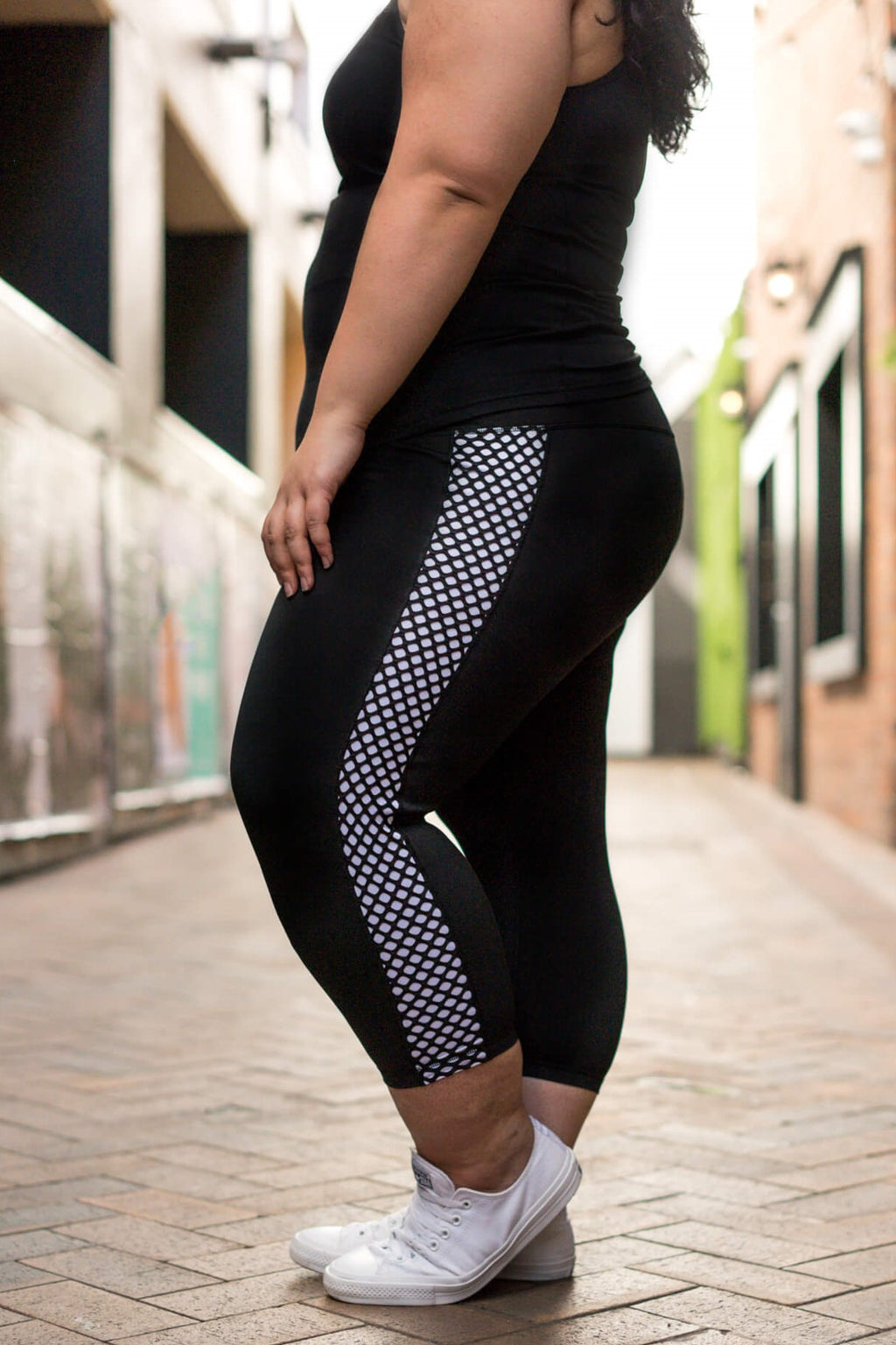 Model is shown from the chest down and wearing black leggings which have a white mesh pattern down the length of each side. The leggings are 7/8 in length, and she also wears a tight black top.