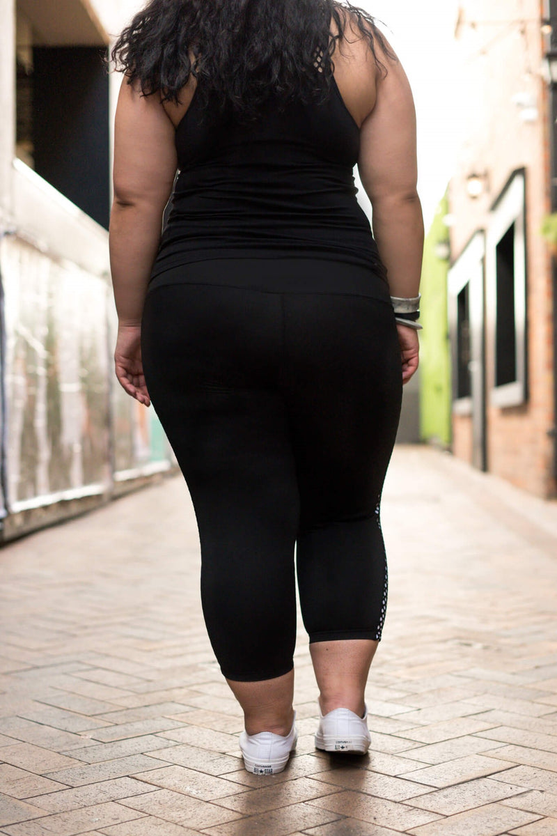 Model is shown from the back and wearing black leggings which have a white mesh pattern down the length of each side. The leggings are 7/8 in length, and she also wears a tight black top.