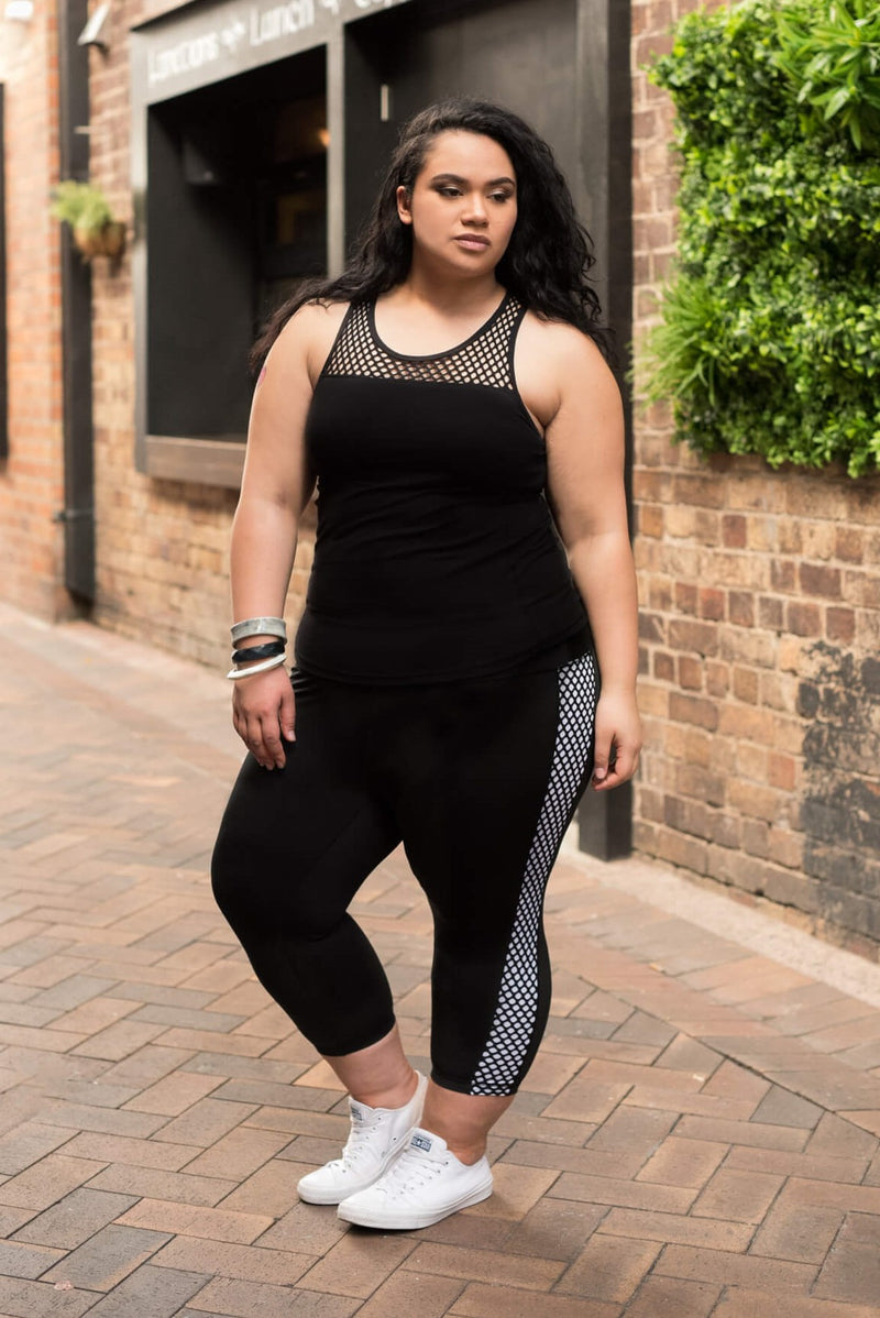 Model is wearing black leggings which have a white mesh pattern down the length of each side. The leggings are 7/8 in length, and she also wears a tight black tank top with a mesh trim on the chest.