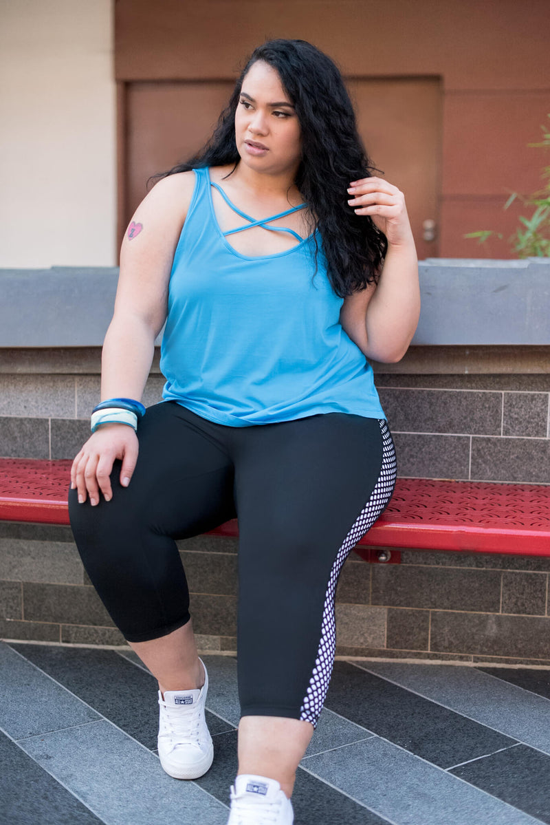 Model is wearing black leggings which have a white mesh pattern down the length of each side. The leggings are 7/8 in length, and she also wears a blue tank top with a crossover on the chest.