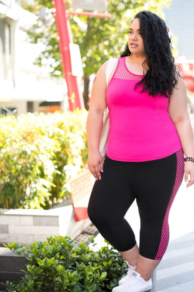 Model is wearing black leggings which have a pink mesh pattern down the length of each side. The leggings are 7/8 in length, and she also wears a tight pink tank top with a mesh trim on the chest.