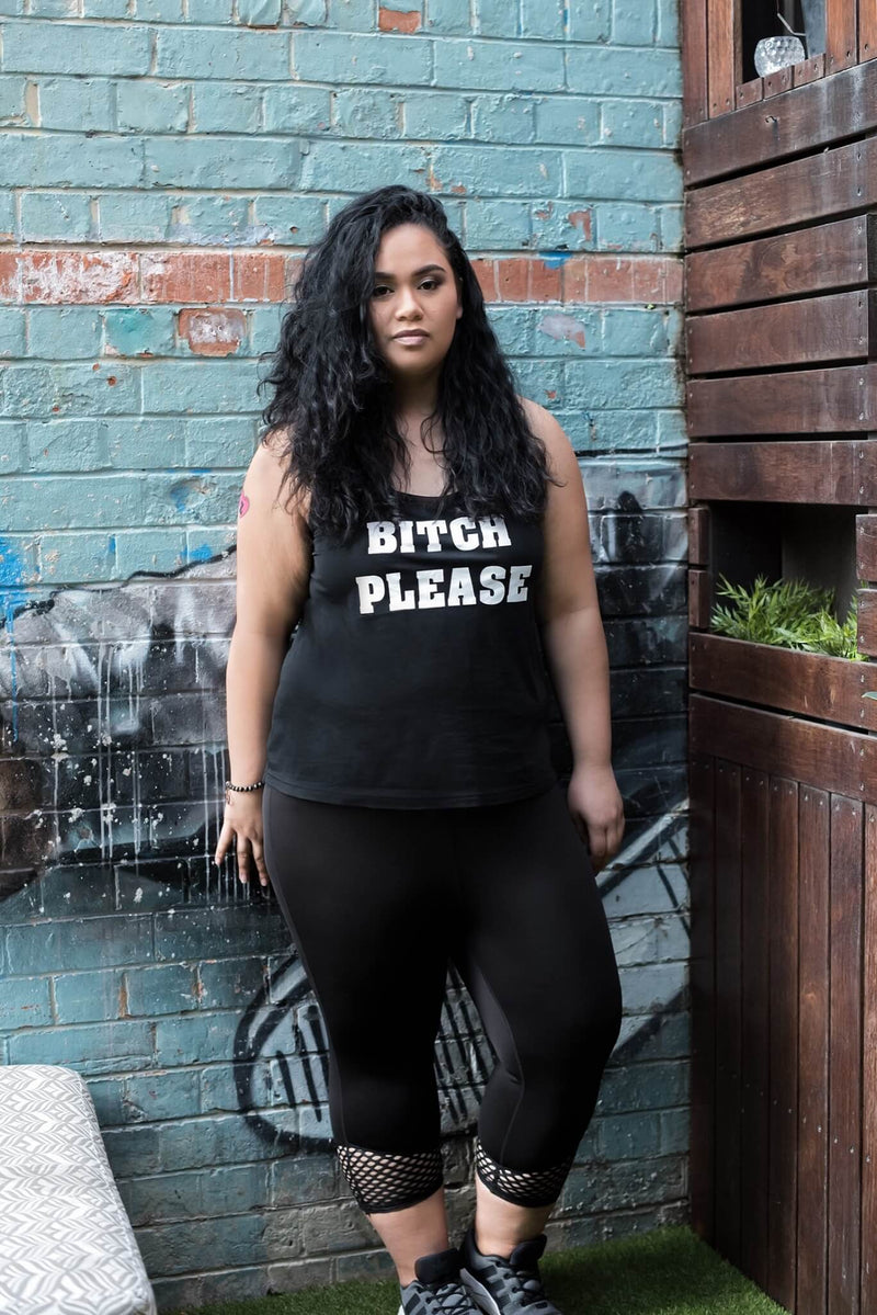 Female model is shown wearing a black tank top, with white lettering on the front reading, 'Bitch Please'. The tank top cuts off at the hips. The model is also wearing black leggings, with mesh cuffs which cut off at approximately 7/8 length.