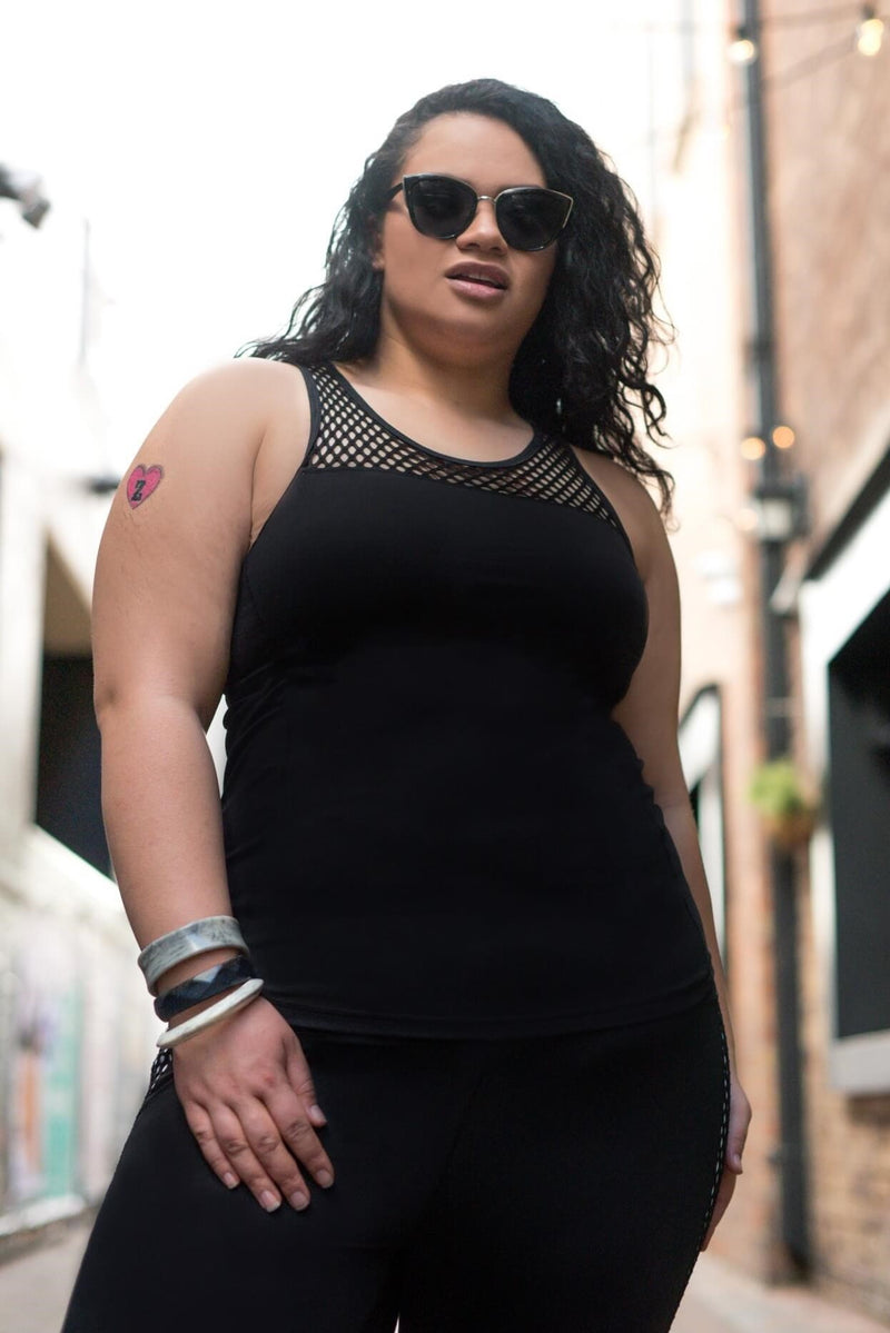 Female model is shown wearing a black tank top with mesh trim at neckline and shelf bra - tight fitting. Worn with black leggings with a panel of white check trim down each side.