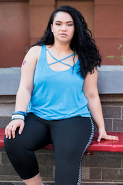 Female model wears blue tank top with cross over feature on neckline, worn with black 7/8 length leggings which have a black and white mesh panel down each side.