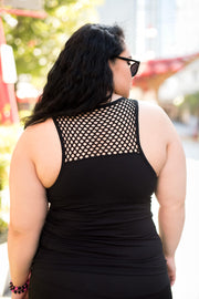 Female model is shown from the back wearing a black tank top with mesh trim at neckline and shelf bra - tight fitting.