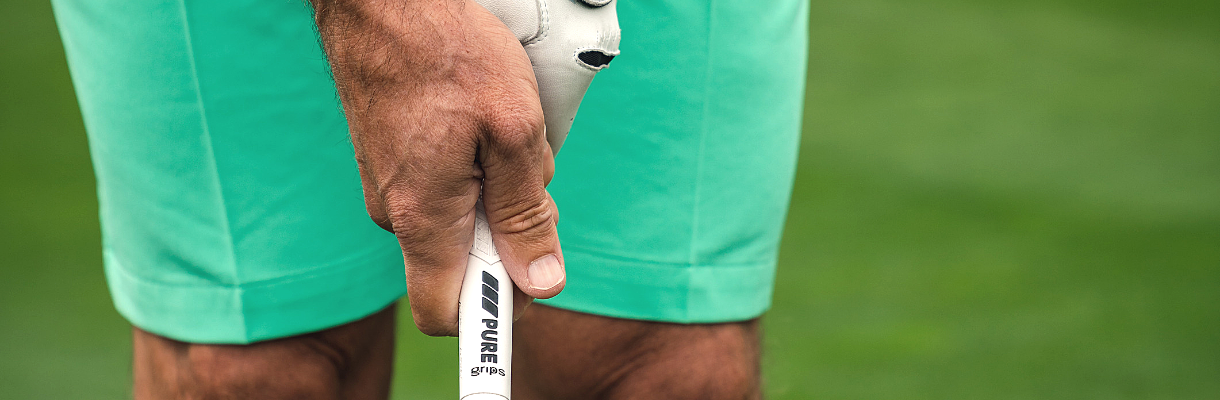 Man in teal shorts gripping PURE DTX grip in Driver White