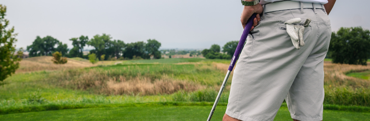 Man in white striped shorts with golf club leaning against his leg