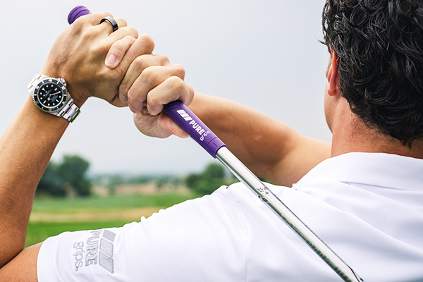 Man in white golf shirt on the backswing of a golf swing using the PURE DTX in Pitch Purple