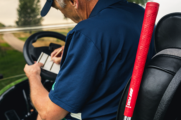 Man in golf cart writing down scores next to PURE DTX grip in Rhythm Red