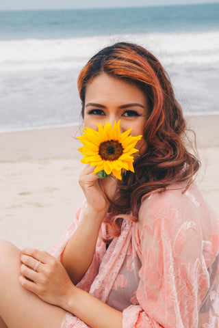 Girl with curly pink hair pink kimono and sunflower in mouth