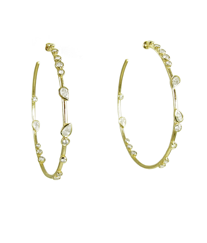 Gold bezeled round and pear shaped diamonds on 53mm round hoops.